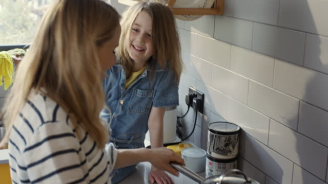 mcu, stabilised handheld - mother and daughter making popcorn in pan - part of a series stock videos & royalty-free footage
