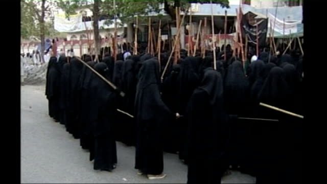 stability of region threatened by benazir bhutto's assassination tx female students wearing burkas demonstrating with sticks outside madrassa... - madressa stock videos and b-roll footage