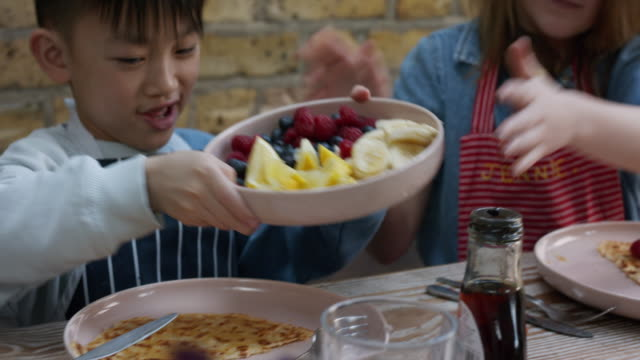 mcu, stabilized handheld - children carefully adding fruit to pancakes - family with two children stock videos & royalty-free footage