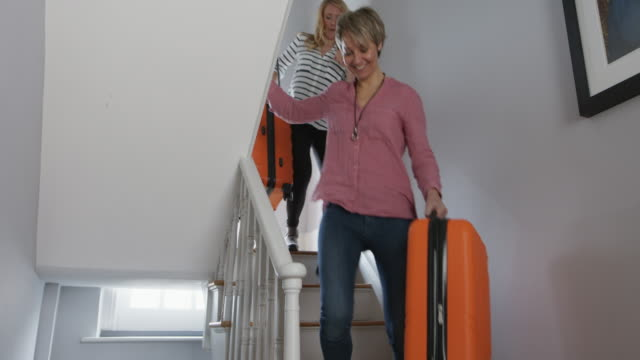 fs, stabilized handheld - family with children walking downstairs with suitcases - staircase stock-videos und b-roll-filmmaterial
