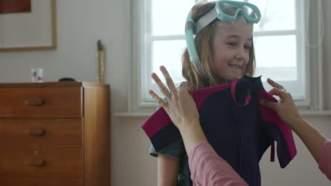 mcu, stabilized handheld - mother checking holiday wet suit for daughter - single mother stock videos & royalty-free footage