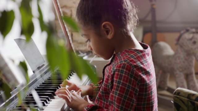 mcu, stabilized handheld - young mixed race girl playing piano - improvement stock videos & royalty-free footage