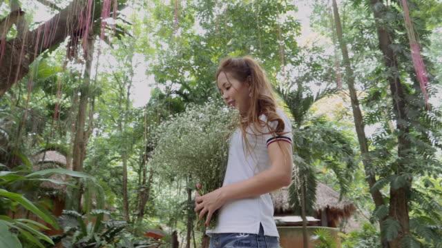 Gestabiliseerde Shot: Aziatische vrouw met witte bloemen staan In de natuur
