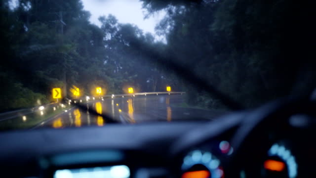 4K Stabilized shot, Man driving in rain on mountain road at dusk.