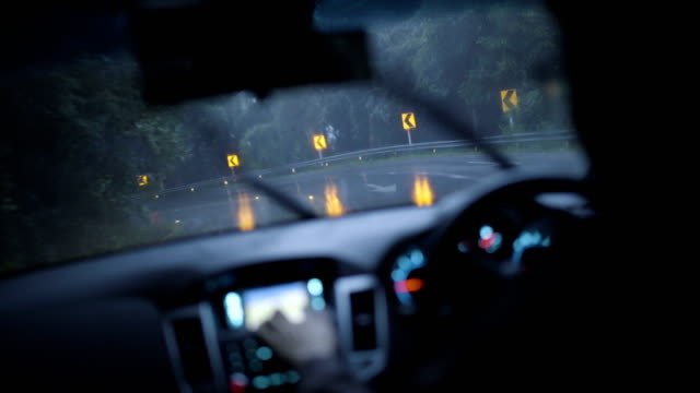 4K Stabilized shot, Man using GPS navigation device while driving in rain at dusk.