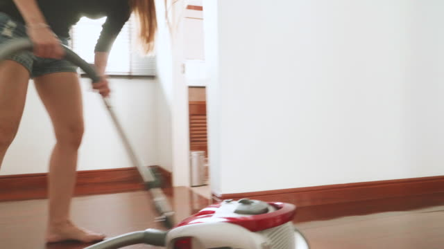 Stabilized Shot Of Women Using Vacuum Cleaner Cleaning On The Ground