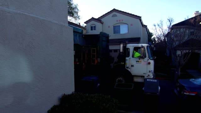 stabilized shot or dolly shot panning from the front porch of a suburban home in san ramon, california to street where waste management garbage truck... - 廃棄物処理点の映像素材/bロール