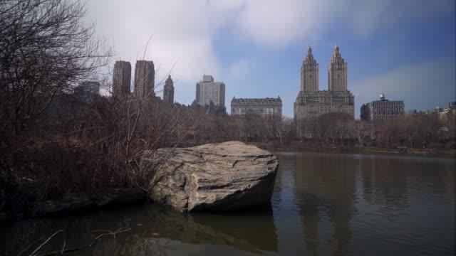 vídeos y material grabado en eventos de stock de stabilizer shot on the water revealing buildings behind rock in central park - central park