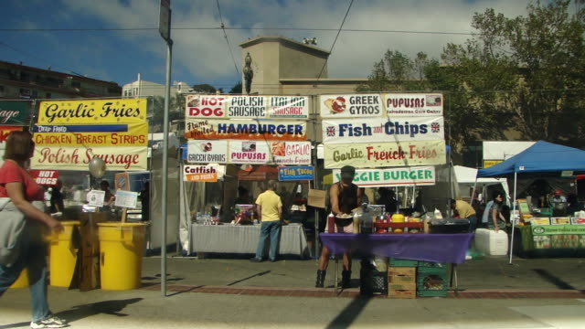 stable view of a row of outdoor food stalls and people walking by signs greek gyros pupusas fish and chips garlic french fries veggie burger hot dog... - french food market stock videos & royalty-free footage