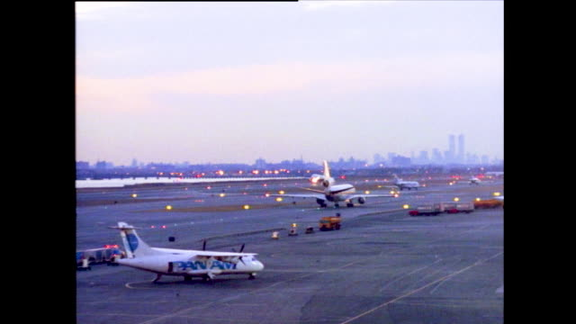 vídeos y material grabado en eventos de stock de stable view of airplanes cruising on a busy runway with the new york city skyline in the background in the dusk/dawn silhouette of twin towers/world... - pasear en coche sin destino