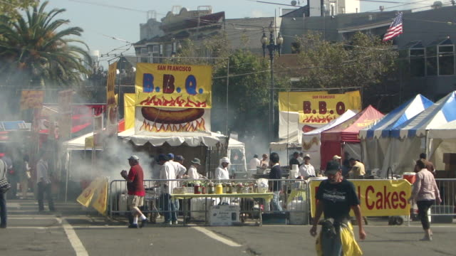 stable view of an outdoor food stall on the street emitting smoke signs san francisco bbq and funnel cakes people walking past the stall and workers... - emitting stock videos & royalty-free footage