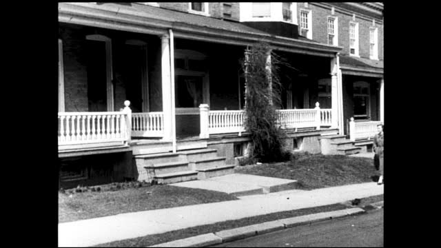 """vidéos et rushes de stable view of building with sign """"western electric allentown plant""""; woman walking down the sidewalk, passing by stores; woman walking down... - 1940 1949"""