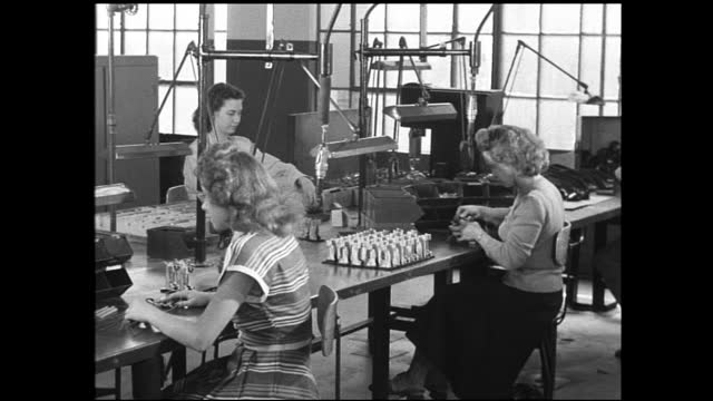 stable view of carpenters working inside factory floor; women workers assembling small components, man in dress shirt walks around and assisting - 1940 1949 stock-videos und b-roll-filmmaterial