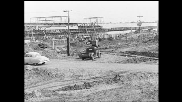 vídeos y material grabado en eventos de stock de stable view of construction site busy with work and truck passes by, leaving trail of dust - 1940 1949