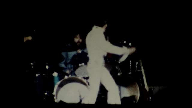 stable view of elvis presley in all white and one red scarf singing and dancing on stage, band with drum and guitars in blue in the background - las vegas stock videos & royalty-free footage