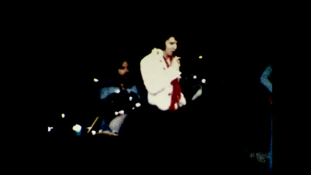 vídeos y material grabado en eventos de stock de stable view of elvis presley in all white and one red scarf singing and dancing on stage, band with drum and guitars in blue in the background and... - actuación espectáculo