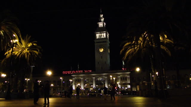 stockvideo's en b-roll-footage met stable view of ferry building with clock tower at night lots of people walking in front of the building and cars passing on the street - veerboothaven