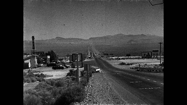 """stable view of highway stretched to the horizon; sign """"death valley""""; from moving vehicle driving through the desert scattered with shrubs; trees in... - death valley national park stock videos & royalty-free footage"""