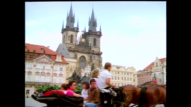 "stable view of horse pulled carriages walking down the street, cars parked on both sides of the road; banner hanging on the street ""imagine black... - prague old town square stock videos & royalty-free footage"