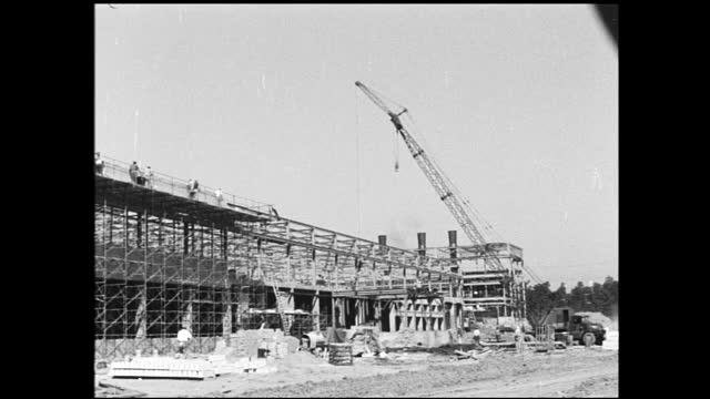 stable view of large building in construction, workers on top of construction site; slate write on blackboard on the dirt; large crane used at... - 1940 1949 bildbanksvideor och videomaterial från bakom kulisserna
