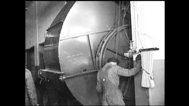 vidéos et rushes de stable view of machinery covered by tape, cardboard, and paper; workers passing by in the background; workers maneuvering metal cylinder shaped... - 1940 1949