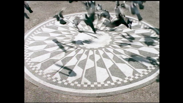 """stable view of metal plate on the ground with the words """"strawberry fields imagine all the people living life in peace ... john lennon"""" and list of... - imagination video stock e b–roll"""