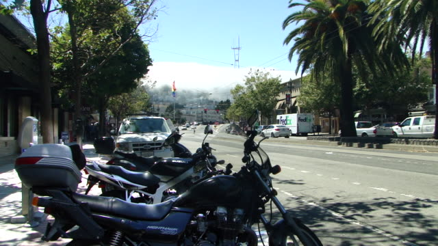stable view of motorcycles and cars parked in the shade by the sidewalk on the street; sutro tower surrounded by fog in the background - stationary stock videos & royalty-free footage