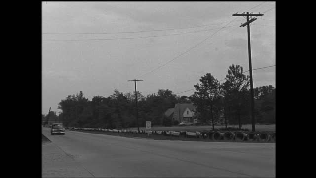 vidéos et rushes de stable view of old clapboard house; grassy pasture with barbed wires and construction site in the background; rural road and car drives by - 1940 1949