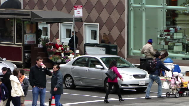 stable view of people crossing the street outdoor flower shop in the background on the sidewalk small santa statue popping up and down in the middle... - flower shop stock videos & royalty-free footage