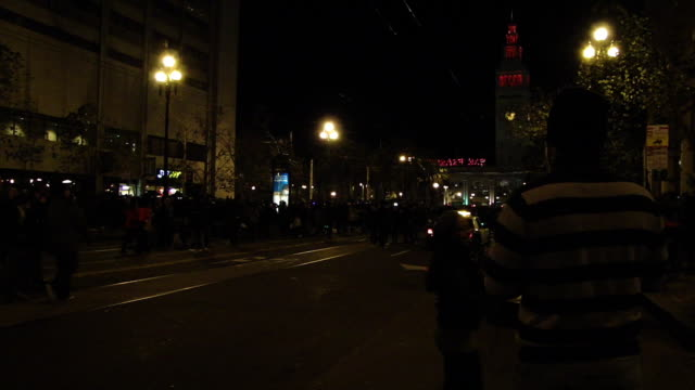 stockvideo's en b-roll-footage met stable view of police car driving down the street in front of the ferry building clock tower at night people marching down the street at the same time - veerboothaven