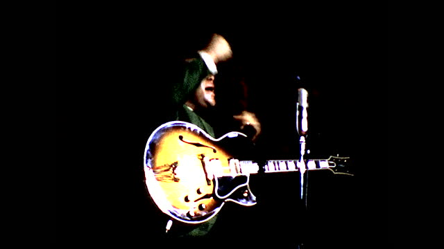 stable view of roy clark in green shirt singing behind the microphone with guitar under the spotlight - 1960 1969 stock videos & royalty-free footage