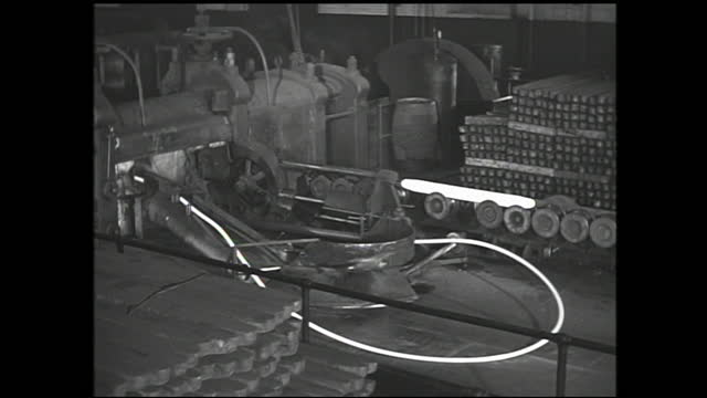 stable view of telephone sitting on the table; overhead crane lifting copper bars; copper bar passing through machinery and is heated and compressed... - 1940 1949 stock videos & royalty-free footage