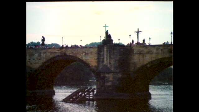 vídeos de stock, filmes e b-roll de stable view of the charles bridge across the river and buildings in the background; closer view of the charles bridge, crowd of people moving... - ponte carlos