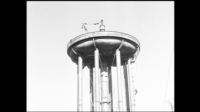 stable view of water tower, telephone cables and poles in the foreground; building under construction; men climbing down of water tower under... - 1940 1949 stock videos & royalty-free footage