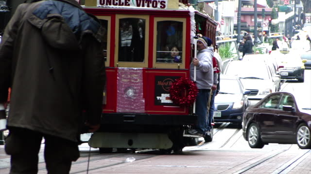 """stable view red cable car with sign """"uncle vito's"""" driving down the street with people hanging off the railings; crowded sidewalk - cable car stock videos & royalty-free footage"""