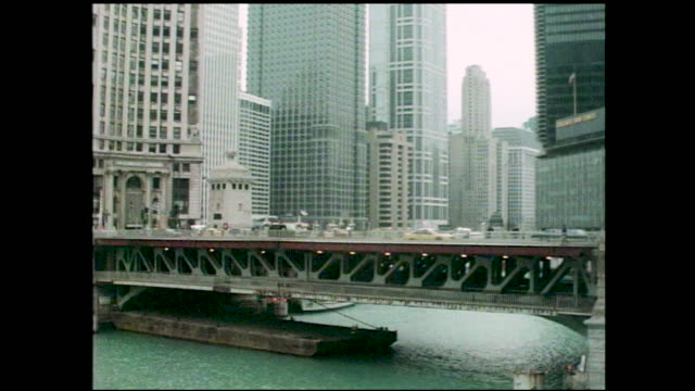 stable views of city skyline; clock tower of the wrigley building and cars passing by on the bridge across the chicago river - レガッタリグレービル点の映像素材/bロール