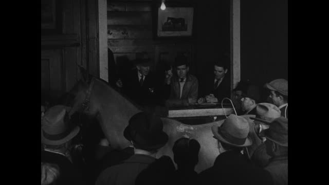 stable w/ sign on building vs horse auctions ext shamrock tavern bar crowded w/ people night old horses being led into back of stable in dark race... - 1910 stock videos & royalty-free footage
