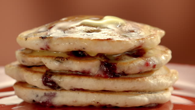 ECU stack of blueberry pancakes as a chunk of butter on top melts and drips over the edges of the pancakes