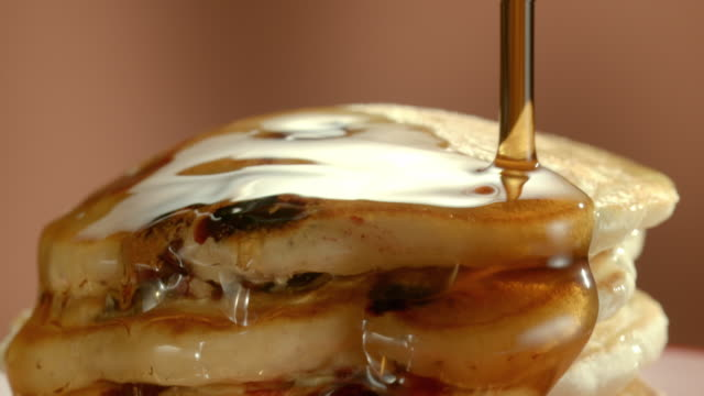 ecu stack of blueberry pancakes as maple syrup is poured over the top and drips along the edges of layered pancakes - pancake stock videos & royalty-free footage