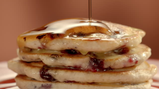 stockvideo's en b-roll-footage met ecu stack of blueberry pancakes as maple syrup is poured over the top and drips along the edges of the pancakes - zoet voedsel