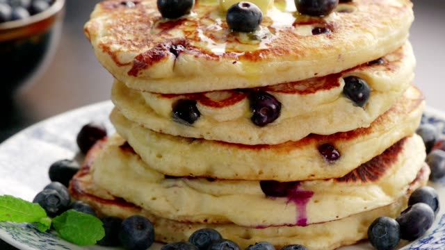 stack of blueberry pancakes with butter and maple syrup - blueberry stock videos & royalty-free footage