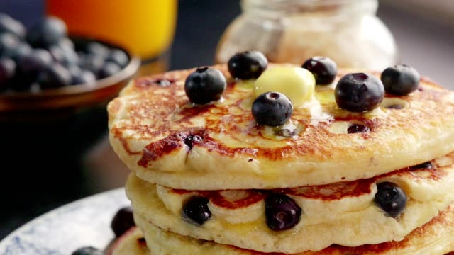 stack of blueberry pancakes with butter and maple syrup - pancake stock videos & royalty-free footage