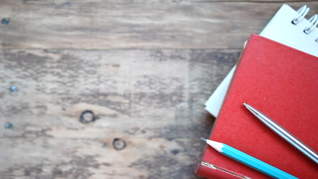 vidéos et rushes de pile de livre avec un stylo sur fond de table en bois - couverture de livre