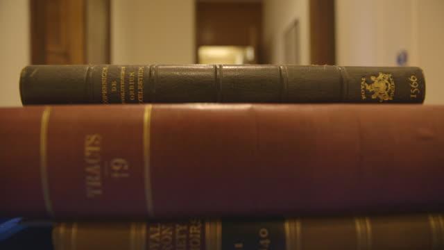 pov stack of books wheeled on trolley in corridor - buchdeckel stock-videos und b-roll-filmmaterial
