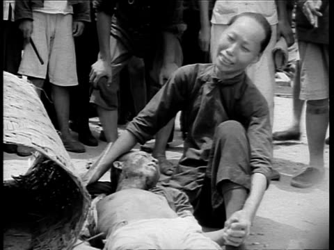 stockvideo's en b-roll-footage met stack of coffins after japanese attack of shanghai / woman crying by dead man / hands lowering lid of coffin on remains / woman crying on rubble by... - 1937