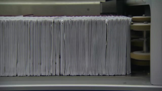 stack of election ballots move quickly through a machine at a ballot processing center in oregon on november 1, 2018. - post structure stock videos & royalty-free footage