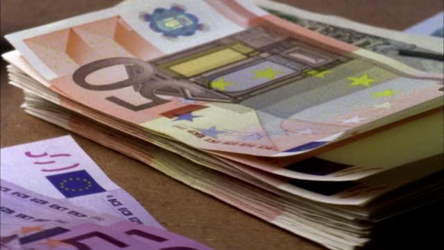 vídeos de stock, filmes e b-roll de ecu, stack of euro and japanese yen bank notes rotating - nota de cinquenta euros