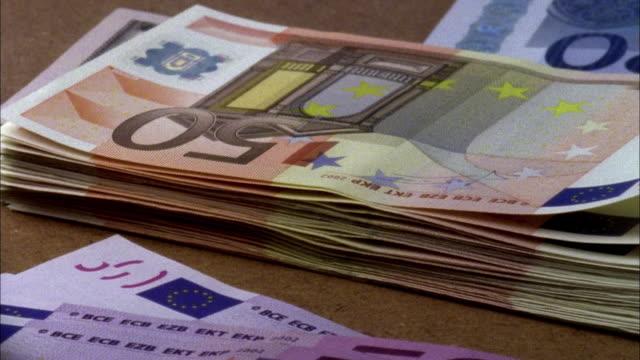 vídeos de stock, filmes e b-roll de ecu, stack of euro banknotes and american dollar banknote rotating - nota de cinquenta euros