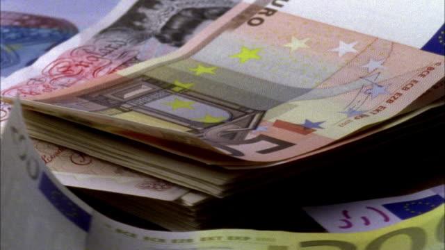 vídeos de stock, filmes e b-roll de ecu, stack of euro banknotes and fifty pounds banknote rotating - nota de cinquenta euros