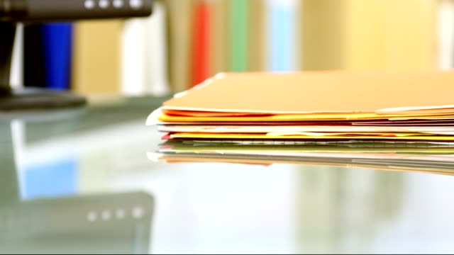 stack of files, documents being piled onto office desk. - human role stock videos & royalty-free footage